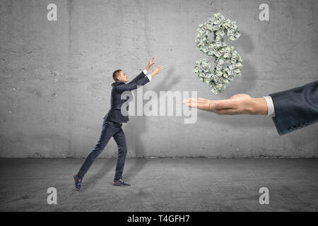 Side view of miniatured businessman holding out hands to grab dollar symbol formed from many banknotes suspended in air above big man's hand. - Stock Photo