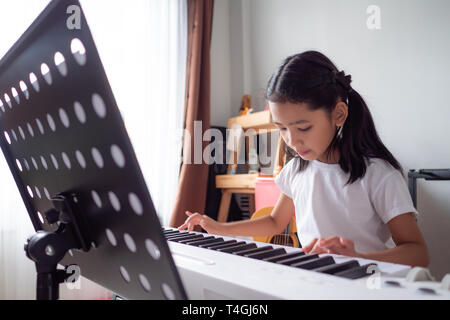 Asian little girl learning to play piano keyboard synthesizer with happiness, Thai girl studying the music at home - Stock Photo
