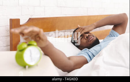 Hand turning off alarm clock waking up at morning