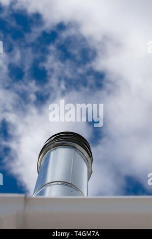 Long chimney pipe reaching into a cloudy blue sky, Bronx, NY - Stock Photo