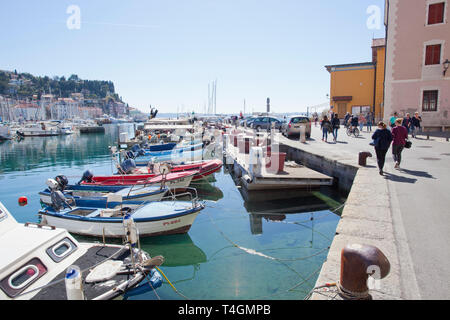People walking alongside boats moored in Piran - Stock Photo