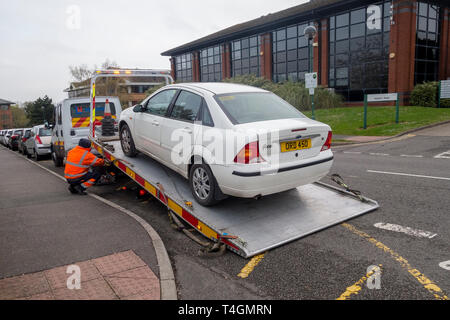 A brokendown car is secured to a recovery vehicle - Stock Photo