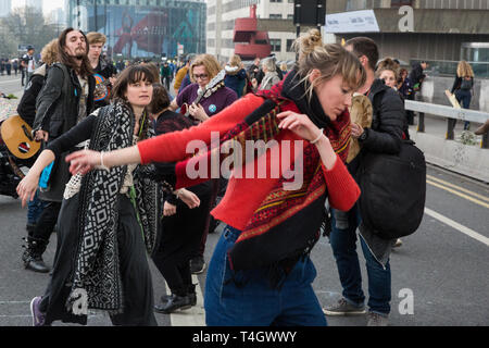 London, UK. 16th April 2019. Climate change activists from Extinction Rebellion dance as they occupy Waterloo Bridge on the second day of Internationa - Stock Photo