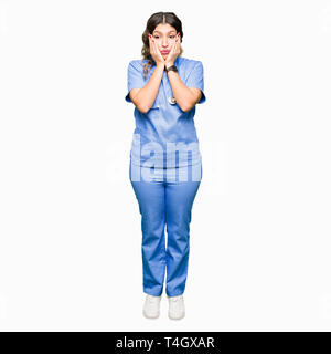 Young adult doctor woman wearing medical uniform Tired hands covering face, depression and sadness, upset and irritated for problem - Stock Photo