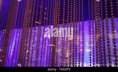 A curtain of small metal beads, hanging in front of a reflective purple and blue background - Stock Photo