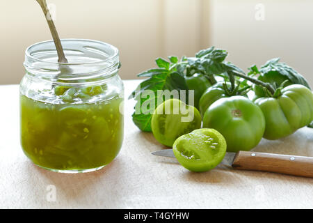 Green tomato jam or chutney in a glass jar with vintage spoon, home canning concept - Stock Photo