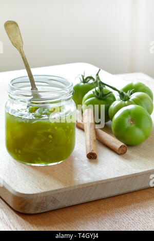 Green tomato jam or chutney in a glass jar with cinnamon flavoring, home canning concept - Stock Photo