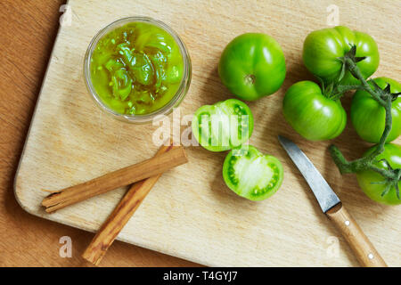 Jam or chutney in a glass jar made of green tomatoes with cinnamon, top view - Stock Photo
