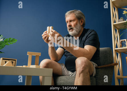 Loosing all the knowledges. Old bearded man with alzheimer desease has problems with his hands motor skills. Concept of illness, memory loss due to dementia, healthcare, neurological disorder, sadness. - Stock Photo