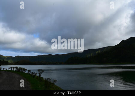 Gray storm clouds hanging over the blue lake of Sete Cidades. - Stock Photo