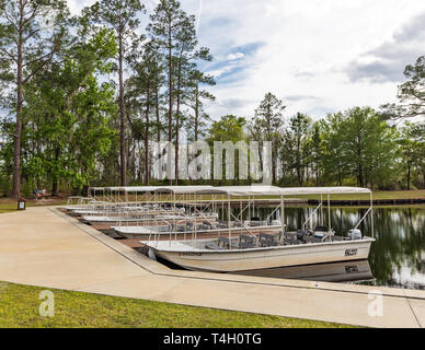 Okefenokee Swamp, Folkston, GA, USA-3/29/19: The canal at eastern entrance to the swamp, with skiffs at dock, and two women in background. - Stock Photo