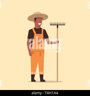 gardener holding rake african american country man working in garden gardening eco farming concept full length - Stock Photo