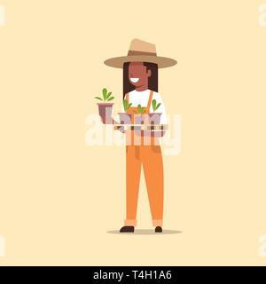 female farmer holding potted plants african american woman in uniform planting young seedlings in garden agricultural worker eco farming concept flat - Stock Photo