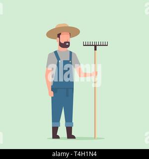 gardener holding rake country man working in garden gardening eco farming concept full length - Stock Photo