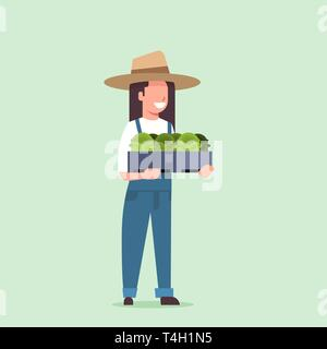 happy female farmer holding box with green fresh lettuce cabbage woman harvesting vegetables agricultural worker in uniform eco farming concept flat - Stock Photo