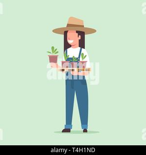 female farmer holding potted plants woman in uniform planting young seedlings in garden agricultural worker eco farming concept flat full length - Stock Photo