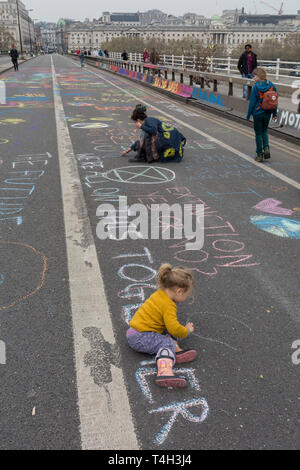 Shildren draw on the road as Climate Change activists with Extinction Rebellion campaign for a better future for planet Earth after blocking Waterloo Bridge and as part of a multi-location 5-day Easter protest around the capital, on 16th April 2019, in London, England. - Stock Photo