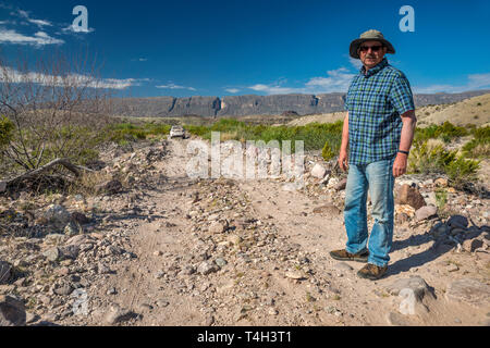 Senior traveler, vehicle on River Road, Sierra Ponce mesa in Mexico in distance, Chihuahuan Desert borderland, Big Bend National Park, Texas, USA