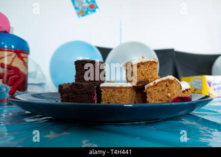 Troon, Scotland, UK - April 14, 2019: Chocolate and Carrot Cake at a Children's Party with branded accesories at the side. - Stock Photo