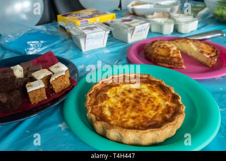 Troon, Scotland, UK - April 14, 2019:Some quiche and part side food  on a party table - Stock Photo