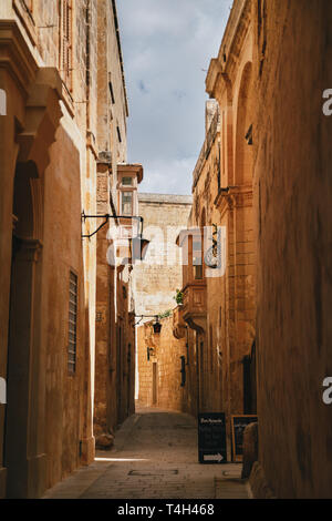 MDINA, MALTA - SEPTEMBER, 15 2018: Yellow narrow medieval street with typical maltese balcony in Mdina, ancient capital of Malta, fortified medieval - Stock Photo