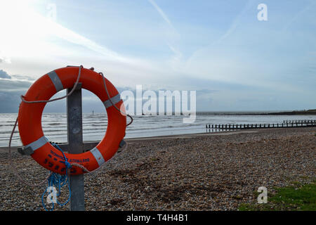 Orange life saving ring attached to a post on Littlehampton seafront - Stock Photo