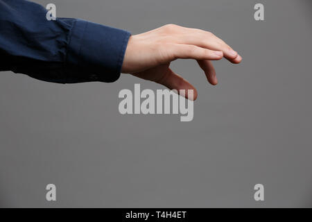 Image of outstretched hand in blue shirt with palm down, holding something with two fingers on empty gray background. - Stock Photo