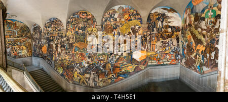 A panoramic view of the stairway mural by Diego Rivera inside the National Palace in Mexico City - Stock Photo