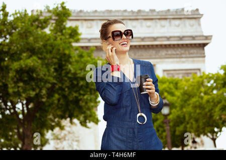 smiling elegant solo traveller woman in sunglasses with coffee cup using a smartphone in Paris, France. - Stock Photo