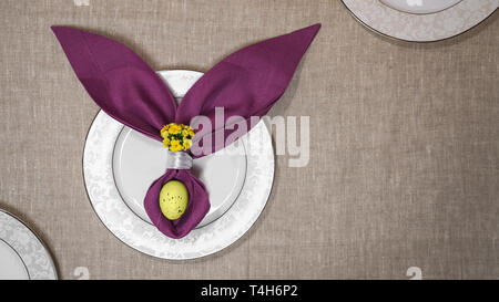 Beautiful Easter table setting with egg, purple napkin Easter Bunny on white plates and on natural tablecloth background. - Stock Photo