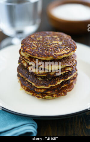 Potato pancakes draniki served on a white plate. Dark wooden table, blue linen napkin, high resolution - Stock Photo