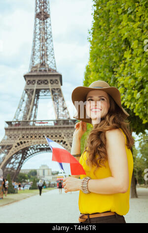 smiling elegant solo traveller woman in yellow blouse and hat with French flag looking into the distance in Paris, France. - Stock Photo
