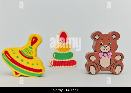 Background of children's colorful wooden toy figures for children on a light background. vertical view - Stock Photo
