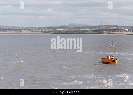 A small little fishing boat is rocked by the waves and windy weather in Morecambe Bay - Winter 2019 - Stock Photo