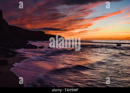 Spectacular, peaceful sunset at low tide, waves breaking over rocks, bright sky reflecting into water, Sunset Cliffs Natural Park, San Diego, CA, USA - Stock Photo