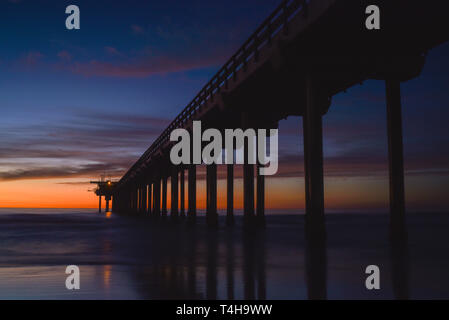 Brilliant sunset with drifting colorful clouds with a silhouette of the cement Scripps Pier with the tide coming in, La Jolla, San Diego, CA, USA. - Stock Photo