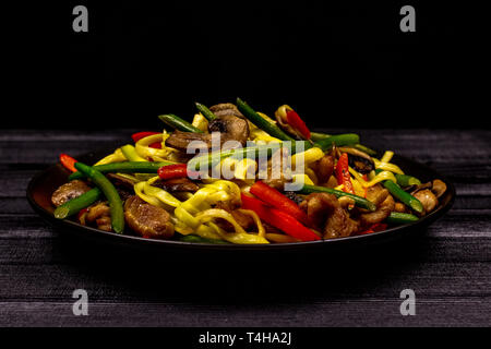 Appetizing stir fried noodles with garlic sprouts, mushrooms, red pepper and chicken meat on a black rustic background of a wooden table. A popular - Stock Photo