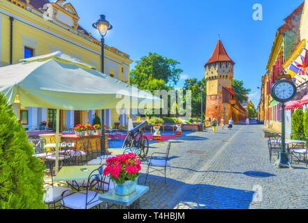 Little square and The Carpenters' Tower in Sibiu city, Transylvania region, Romania. - Stock Photo