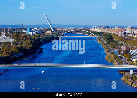 Elevated view of modern bridges spanning the 'Canal de Alfonso XIII' in Seville at sunset - Stock Photo