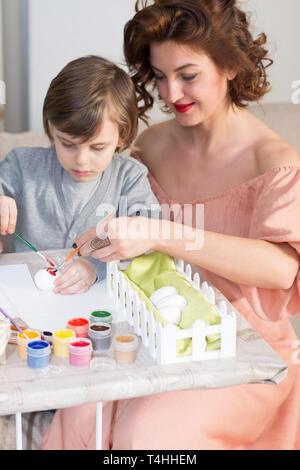 Easter celebration with children doing funny activities like painting eggs and faces - Stock Photo