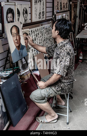 Artist paints vintage portrait of Mao. Chinese man of the Dafen Village at work. Residents specialize in copying and replicas of famous oil paintings. - Stock Photo
