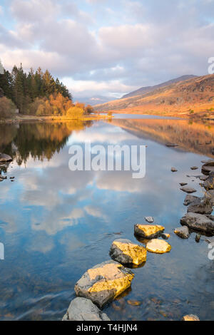 Scenic morning view of Snowdon Horseshoe mountains in clouds, reflected in the still water of Llynnau Mymbyr, Snowdonia National Park, North Wales, UK