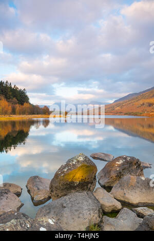 Scenic morning view: welsh Snowdon Horseshoe mountains in clouds, reflected in still water of Llynnau Mymbyr, Snowdonia National Park, North Wales, UK.