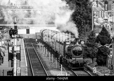 Black & white, bird's-eye view of vintage steam train on SVR heritage railway line leaving Kidderminster station, puffing on the track. Good old days. - Stock Photo