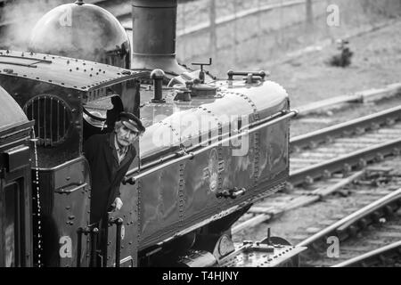 Black & white bird's-eye close up of vintage UK steam locomotive on railway track pulling into station; train crew driver, in cap, looks up out of cab. - Stock Photo