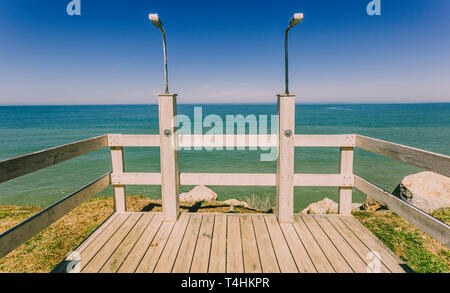 Public showers with wooden gazebo on a cliff on the beach.