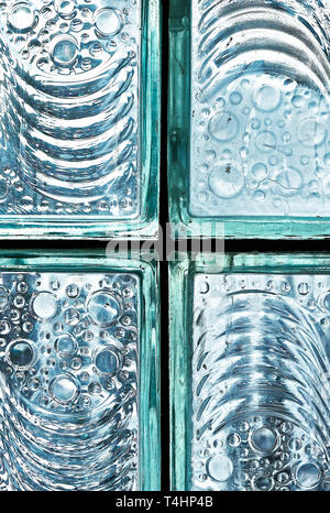 Detail of fixed blue colored glass block bricks with texture of flowing lines and bubbles, photographed against the cool bright light - Stock Photo