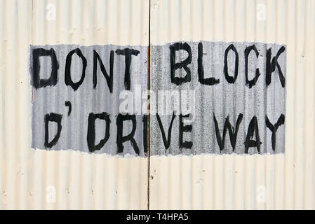 Closed gate of corrugated metal with written sign 'Don't block the driveway'. The gate is newly painted in white color, but the writing is spared. - Stock Photo