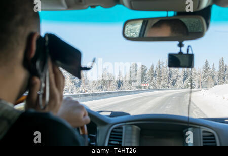 Caucasian man talking on the phone while driving a car on a slippery snow covered road in the taiga - Stock Photo