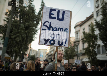 Athen, Greece. 16th Apr, 2019. A man is holding a sign with the words: 'EU, be ashamed' during a demonstration organised by members of anti-racist organisations and trade unions against the expulsion of refugees. Credit: Socrates Baltagiannis/dpa/Alamy Live News - Stock Photo